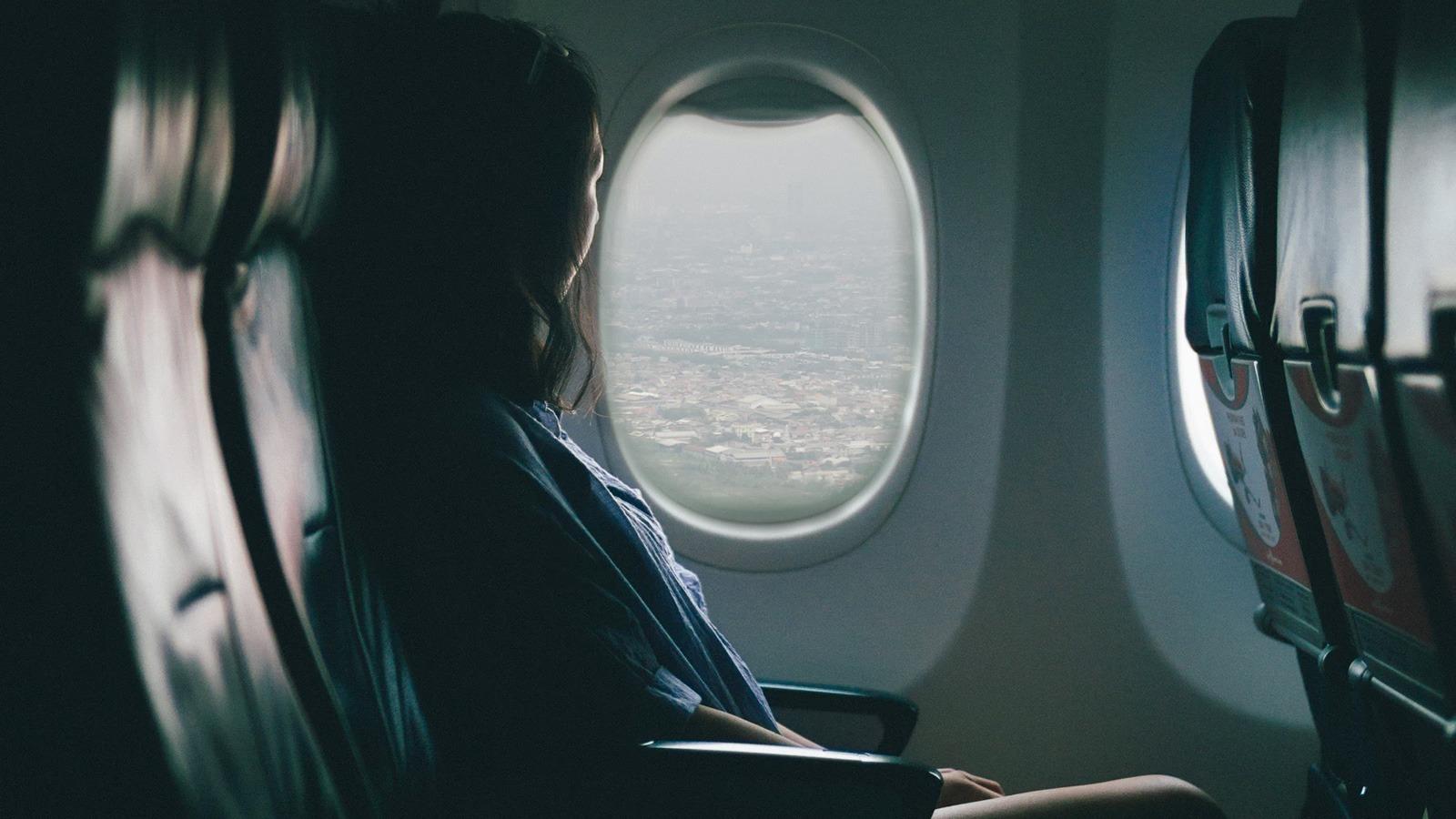 Une femme assise dans l'avion regarde par le hublot