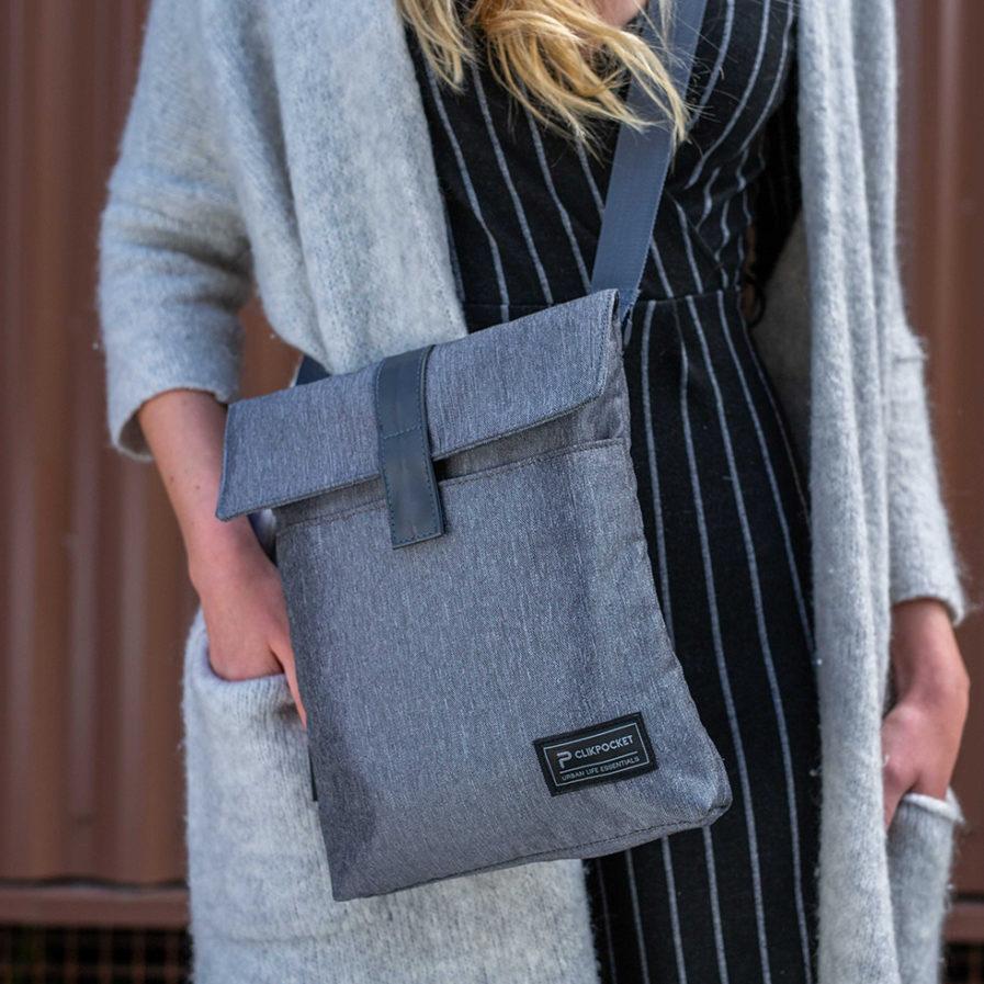 Gros plan sur le sac bandoulière Clikpocket Baby Station gris portée par une femme