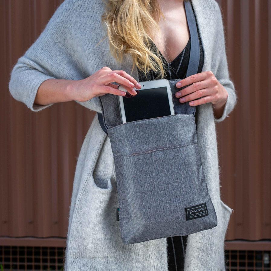 Sac bandoulière Clikpocket Baby Station gris portée par une femme qui range sa tablette à l'intérieur