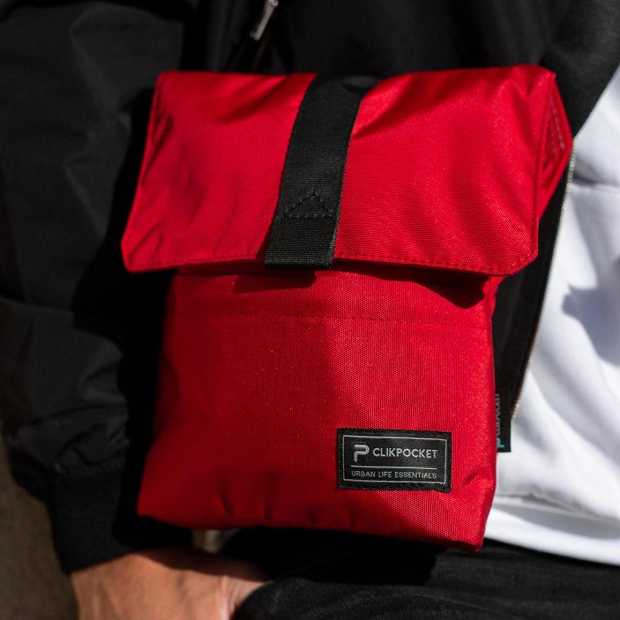 Gros plan sur la pochette bandoulière Clikpocket Check In rouge portée par une homme