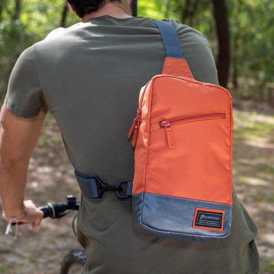 Gros plan sur le sac bandoulière Clikpocket Downtown PAD tangerine porté par une homme à vélo dans la forêt