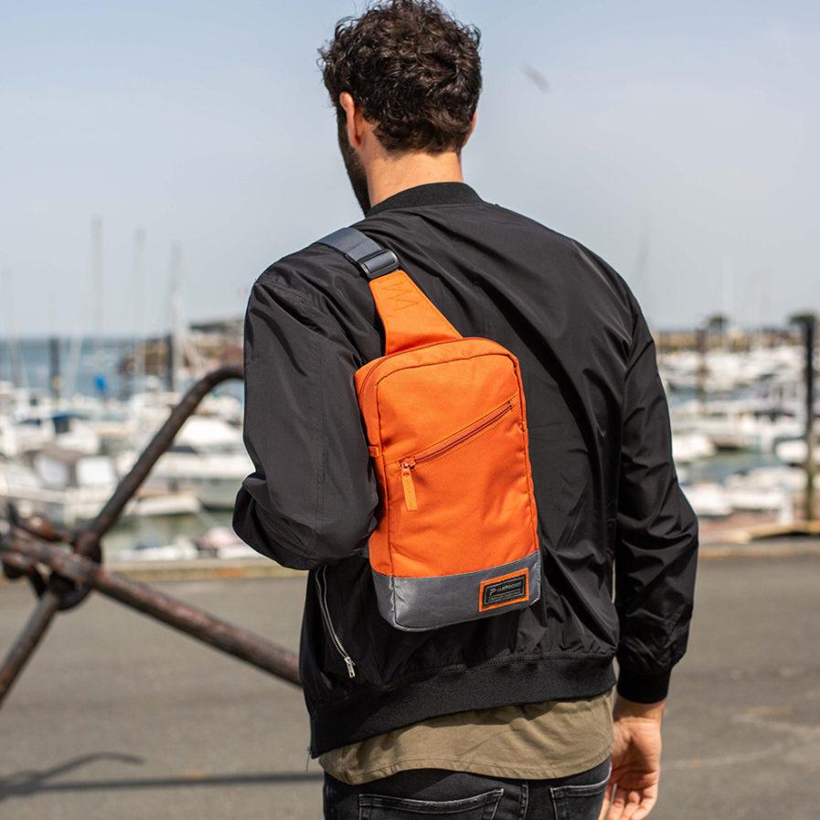 Sac bandoulière Clikpocket Downtown PAD tangerine porté par une homme qui marche en bord de mer