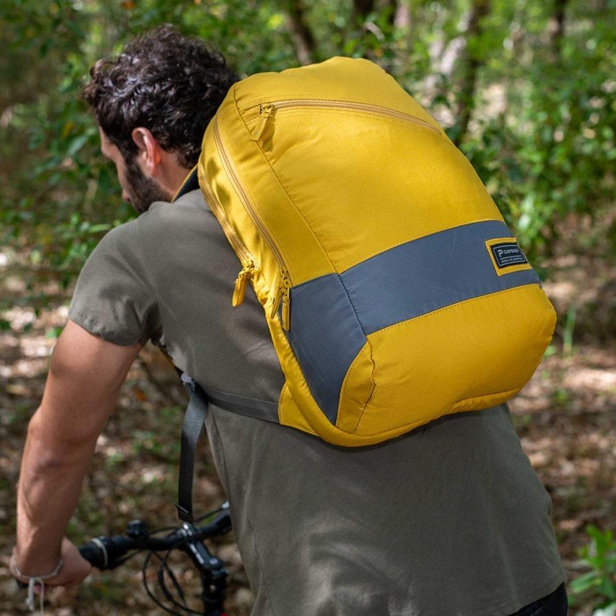 Sac à dos Clikpocket Downtown World Safran porté par un homme à vélo dans la forêt