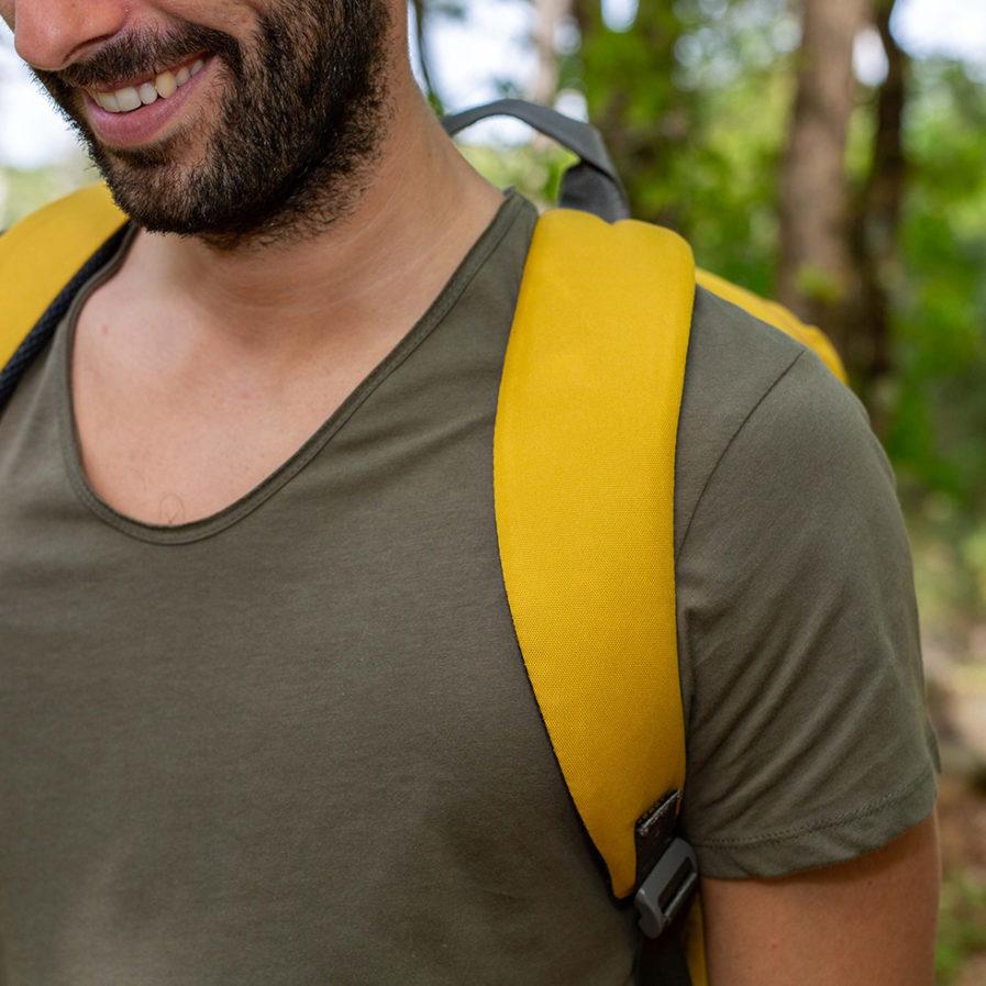 Gros plan sur les bretelles du sac à dos Clikpocket Downtown World Safran porté par un homme dans la forêt