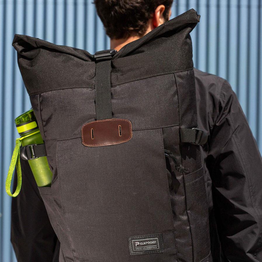 Gros plan sur le sac à dos Clikpocket Nomad noir porté par un homme de dos