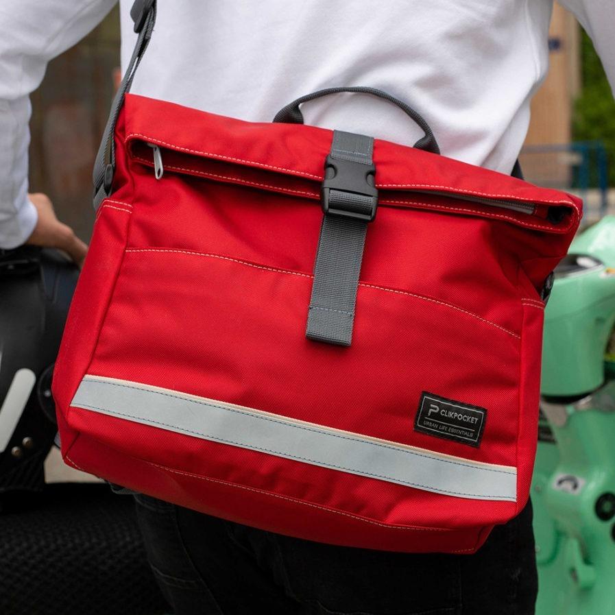 Gros plan sur le sac multi-usages Clikpocket Ride On Bike Rouge portée par un homme en 2 roues