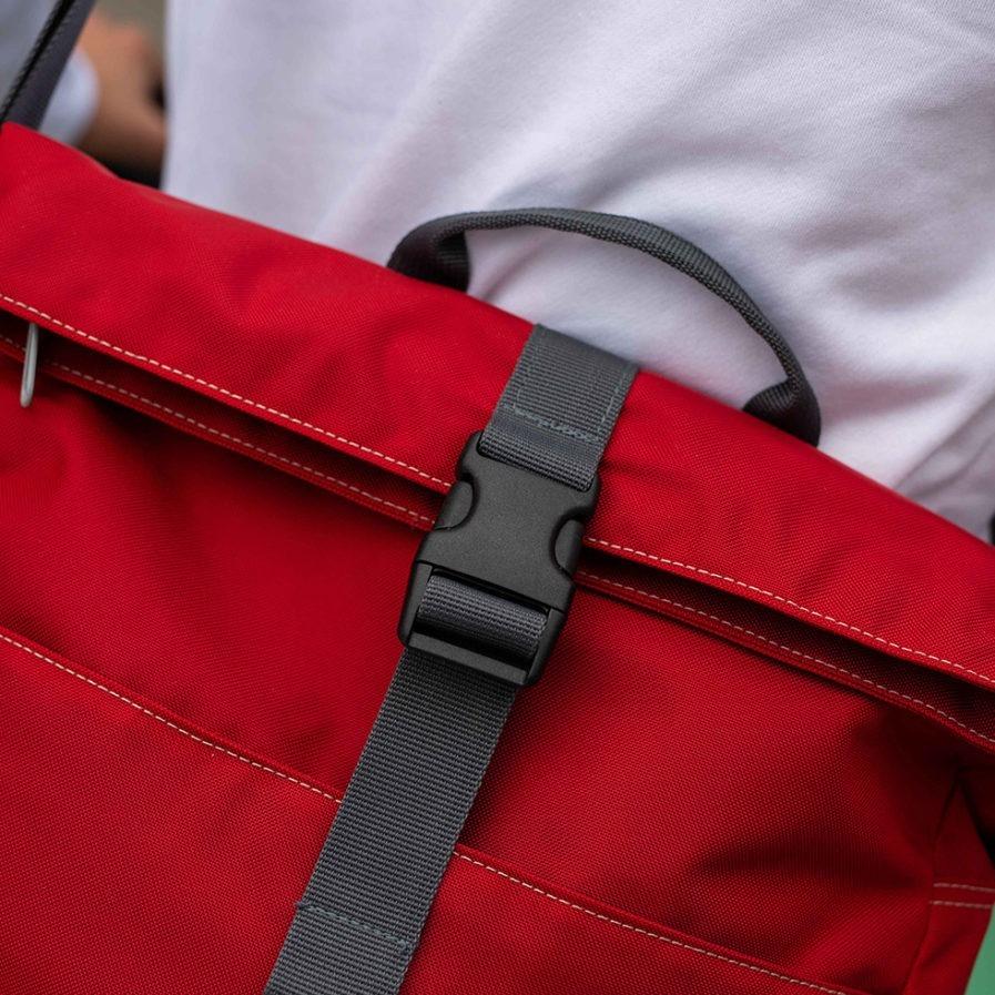 Très gros plan sur le sac multi-usages Clikpocket Ride On Bike Rouge portée par un homme en 2 roues