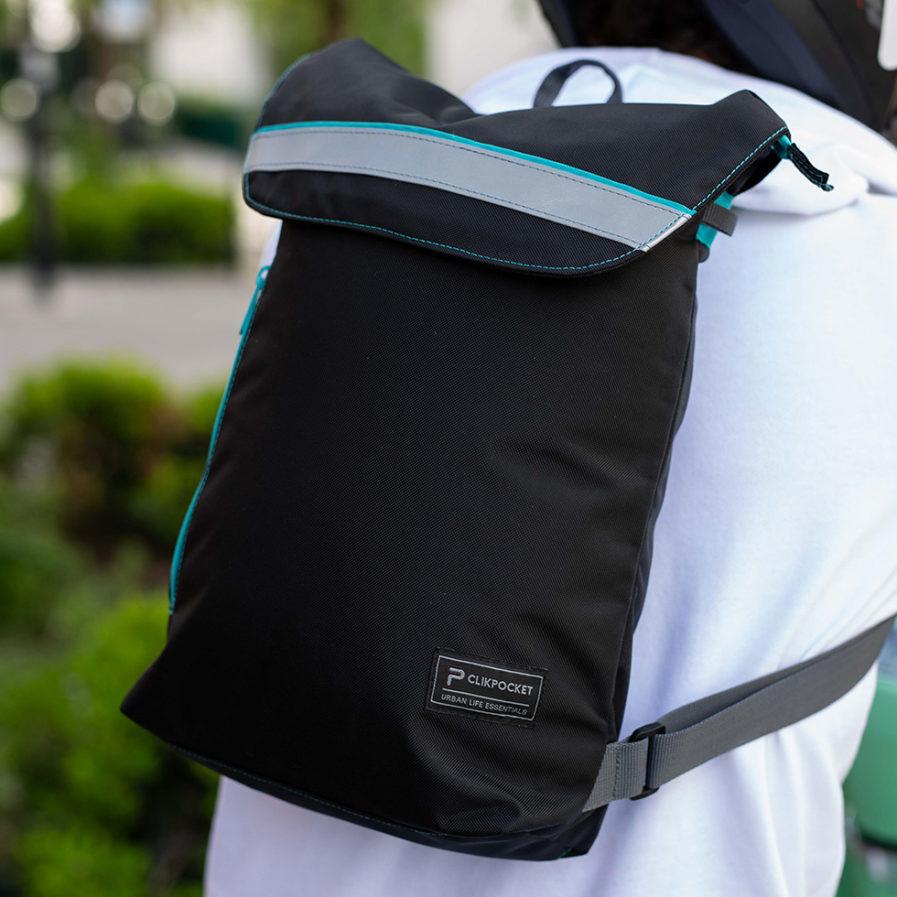 Gros plan sur le sac à dos Clikpocket Ride On City porté par un homme en 2 roues