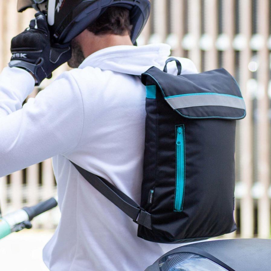 Sac à dos Clikpocket Ride On City porté par un homme en 2 roues qui met son casque