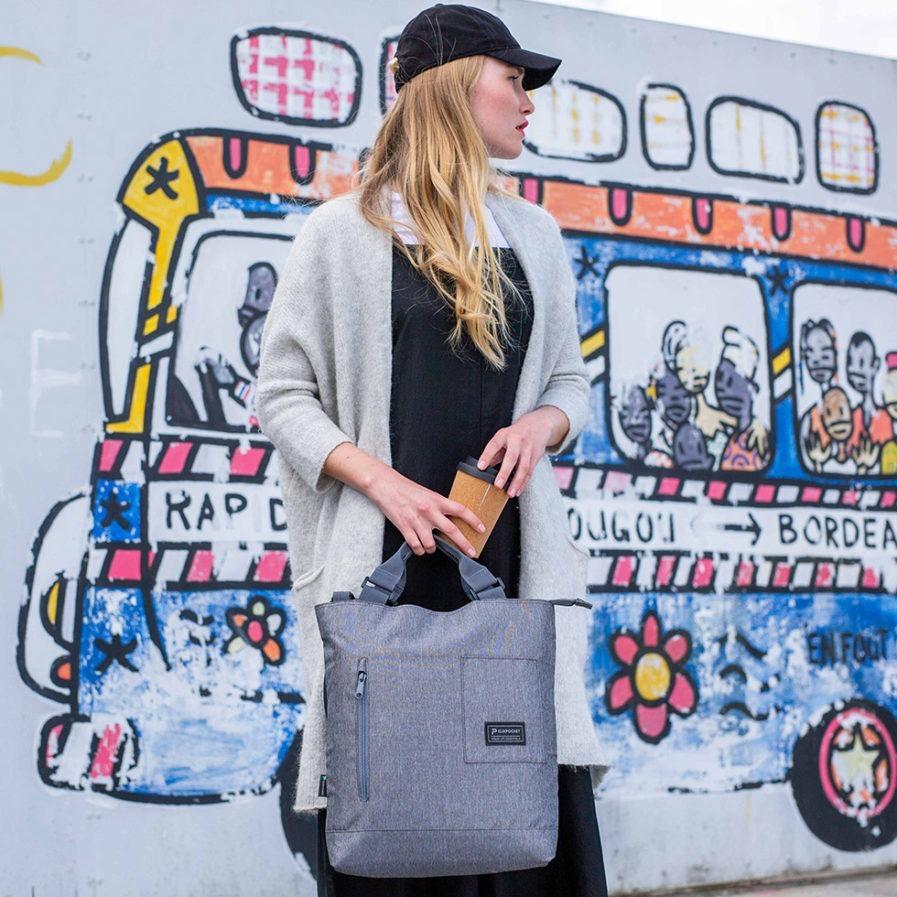 Sac à main bandoulière Clikpocket Station gris portée par une femme devant un mur urbain