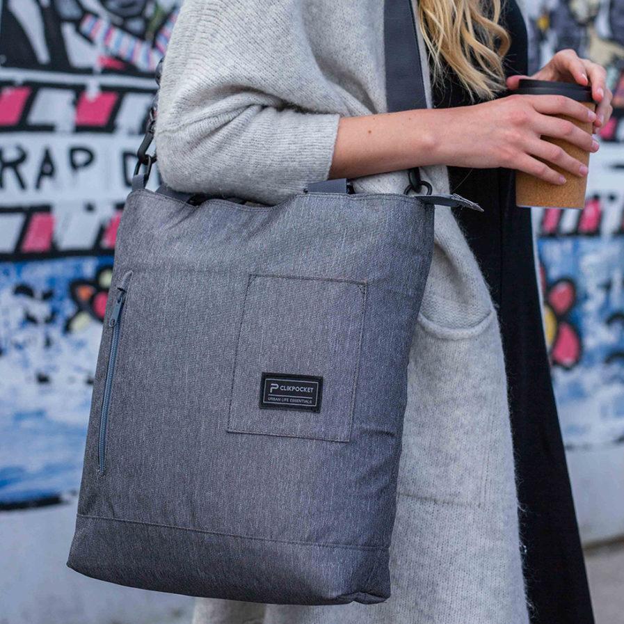 Gros plan sur le sac à main bandoulière Clikpocket Station gris portée par une femme devant un mur urbain