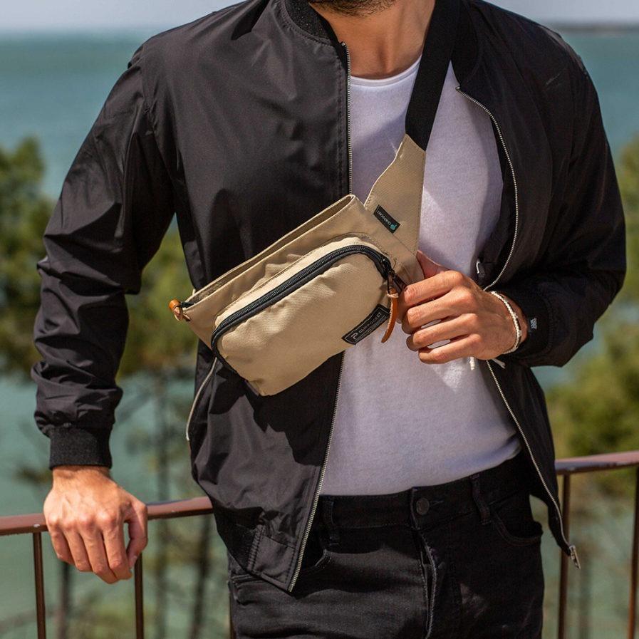 sac banane clikpocket travel beige porté en bandoulière par un homme en bord de mer