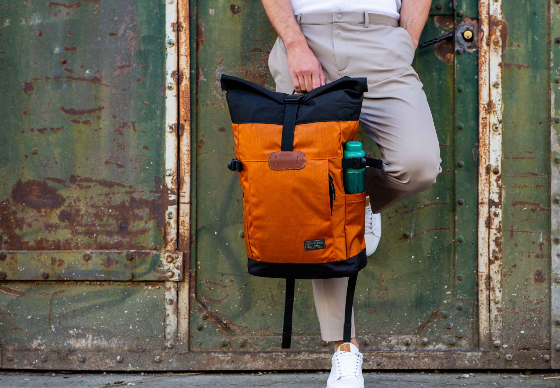 Sac à dos Clikpocket Nomad cuivre porté à la main par un homme en milieu urbain