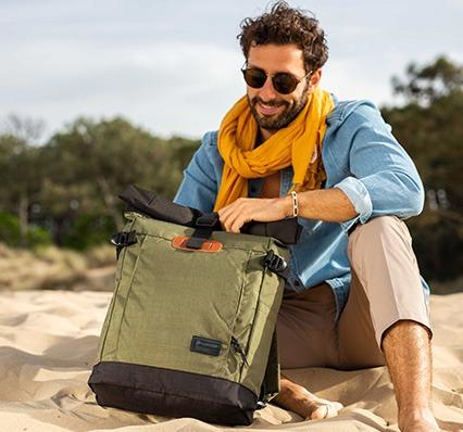 Vignette d'un homme assis sur la plage ouvre son sac à dos Clikpocket Nomad vert