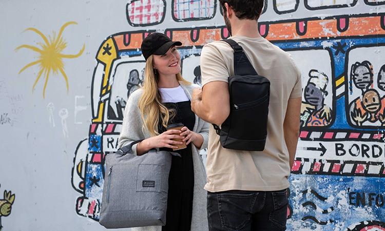 Vignette d'une femme portant le sac à main Station gris souriant à un homme portant le sac bandoulière Downtown Pad noir