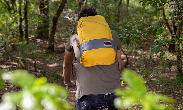 Vignette du sac à dos Clikpocket Downtown World Safran porté par un homme à vélo dans la forêt