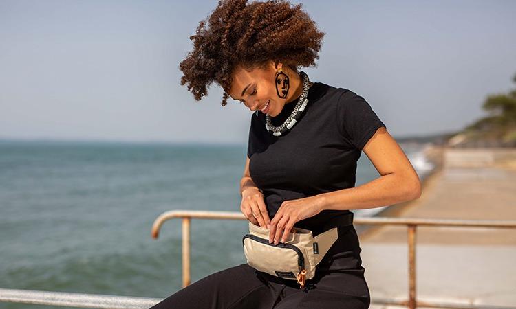 Vignette du sac banane clikpocket travel beige porté par une femme qui ferme la pochette