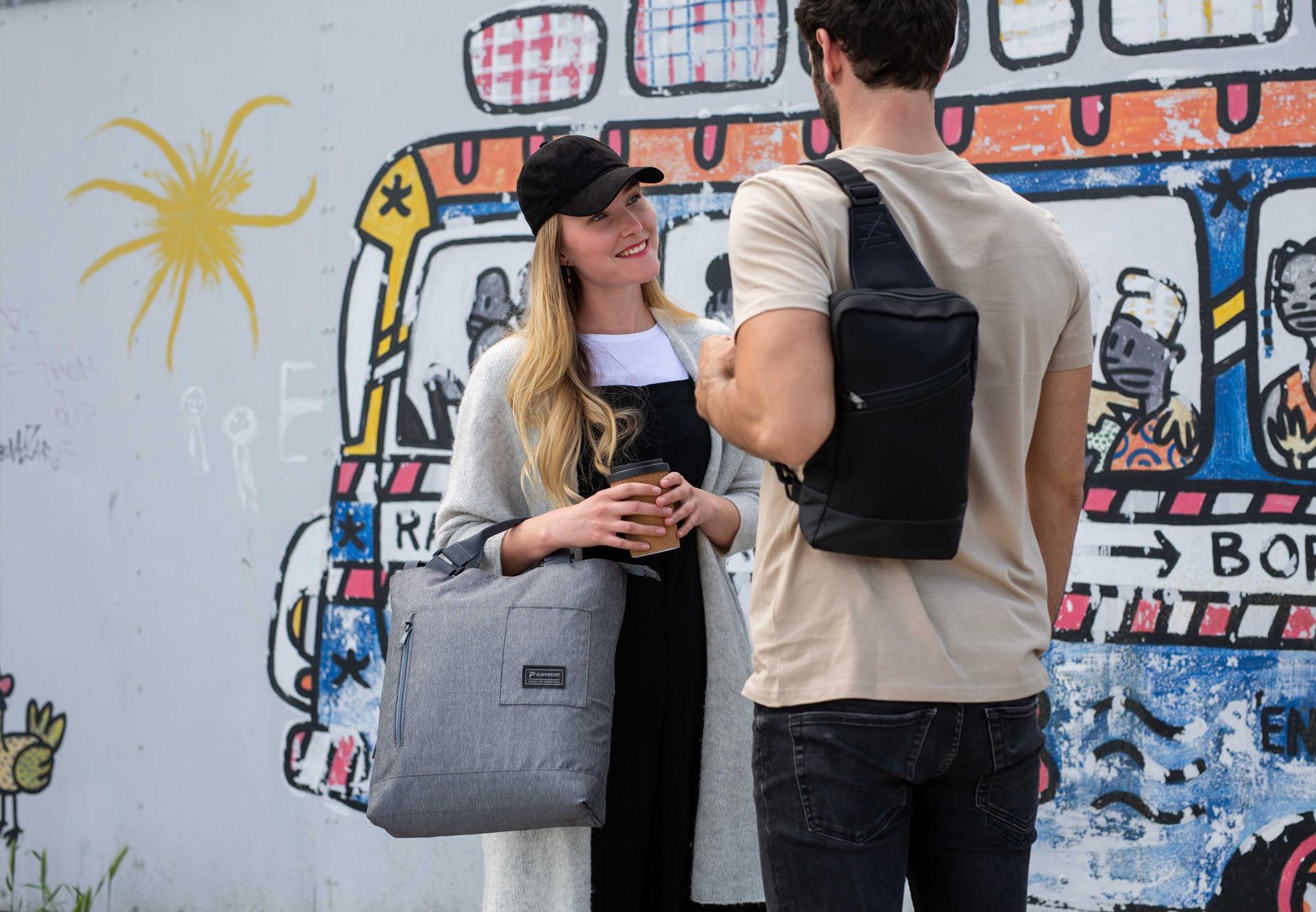 Une femme portant le sac à main Station gris souriant à un homme portant le sac bandoulière Downtown Pad noir